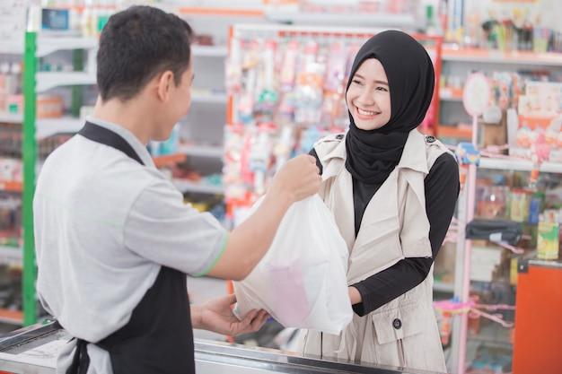 Weiblicher muslimischer kunde im supermarkt