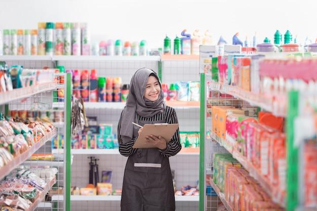 Weiblicher muslimischer ladenbesitzer, der am supermarkt arbeitet