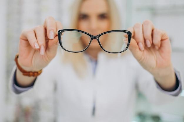 Weiblicher optiker, der am optischen geschäft arbeitet