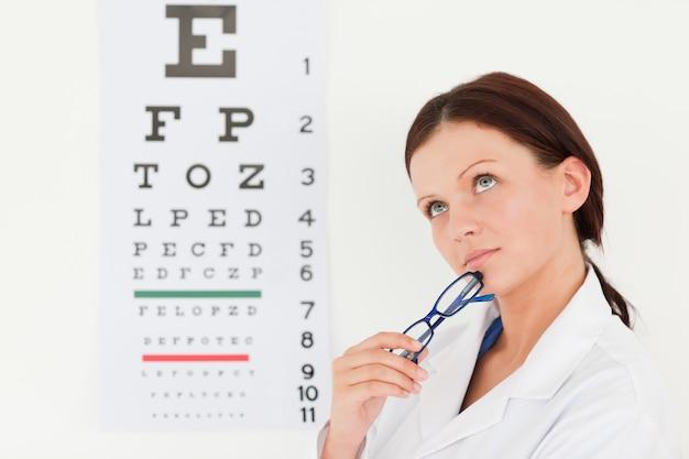 Weiblicher optiker mit sehtest im büro