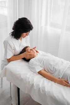 Weiblicher osteopath, der ein kind behandelt
