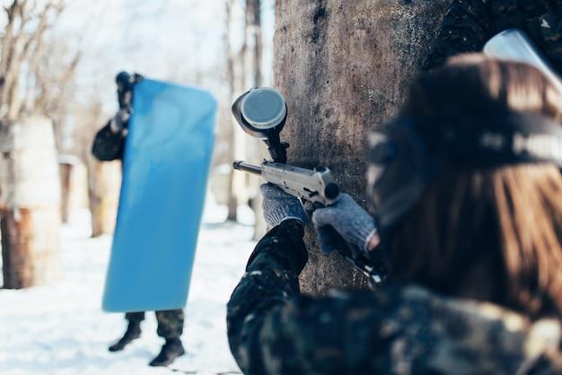 Weiblicher paintballspieler, der auf den feind mit dem schild, rückansicht, winterwaldschlacht schießt. extremsportspiel, spieler kämpfen in schutzmasken und uniform