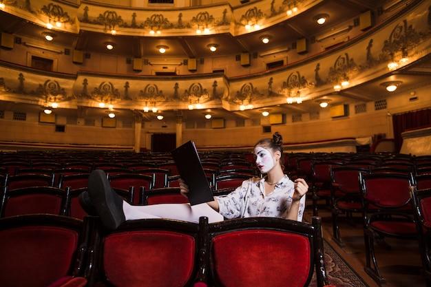 Weiblicher pantomime, der auf stuhllesehandschrift sitzt