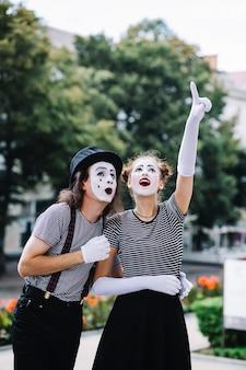 Weiblicher pantomime, der aufwärts zeigend etwas zum männlichen pantomimen zeigt