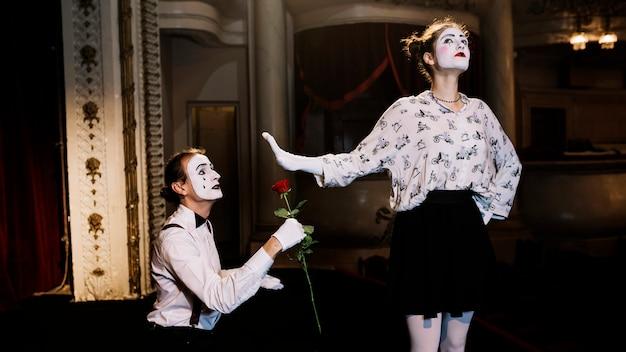 Weiblicher pantomime, der dem männlichen pantomimekünstler zeigt, der rote rose hält, stoppen sie geste