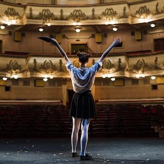 Weiblicher pantomime, der ihre arme im auditorium anhebt