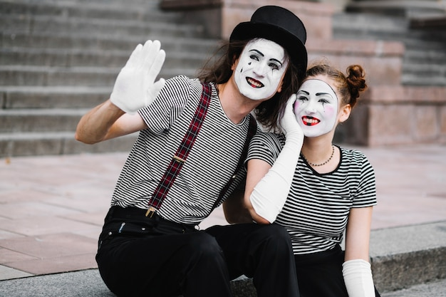 Weiblicher pantomime, der mit dem männlichen pantomimen gestikulieren auf wiedersehen sitzt