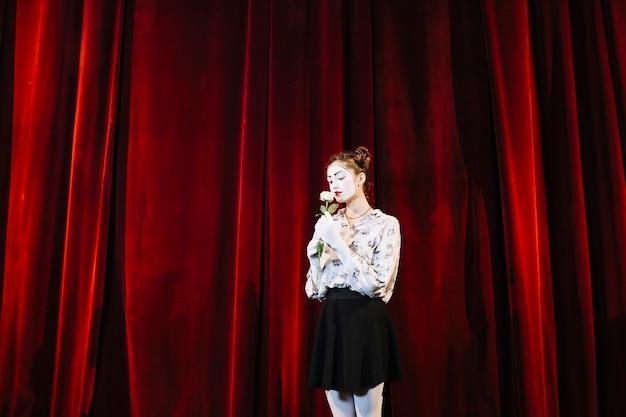 Weiblicher pantomime, der vor riechender weißrose des roten vorhangs steht
