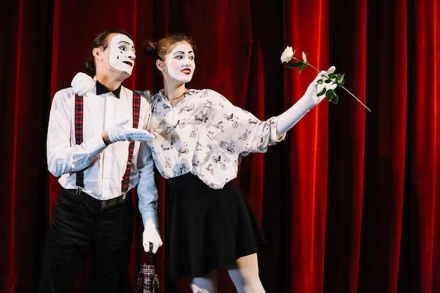 Weiblicher pantomime, der weißrose steht mit männlichem pantomimen hält
