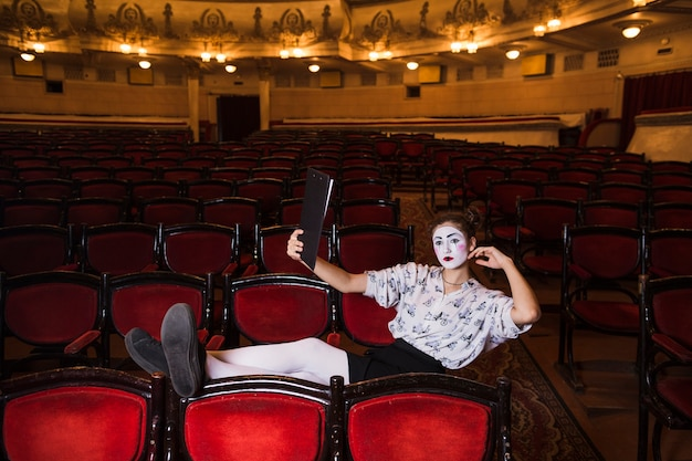 Weiblicher pantomime mit dem manuskript, das auf stuhl sitzt