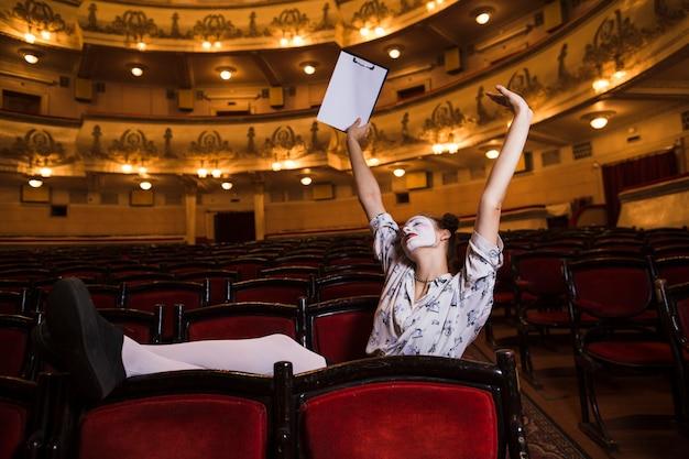 Weiblicher pantomime mit dem manuskript, das ihre arme ausdehnt