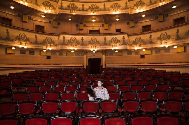 Weiblicher pantomime mit dem manuskript, das in der mitte des auditoriums sitzt