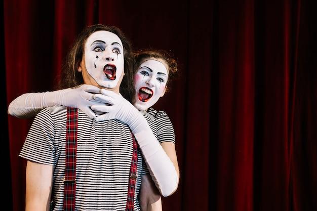 Weiblicher pantomimekünstler, der den hals des männlichen pantomimen ergreift