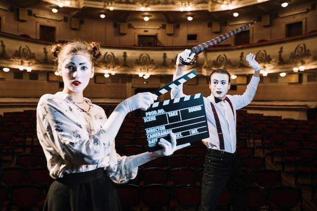 Weiblicher pantomimekünstler, der klöppel vor dem männlichen pantomimen hält regenschirm hält