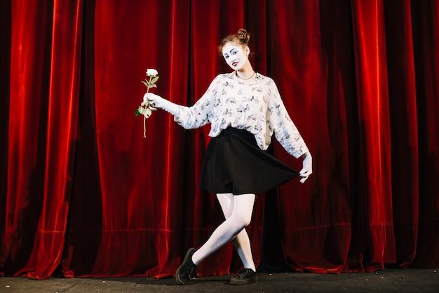 Weiblicher pantomimekünstler, der mit dem gekreuzten bein hält weißrose steht