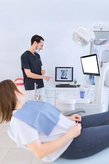 Weiblicher patient, der auf dem zahnarztstuhl betrachtet zahnröntgenstrahl auf schirm liegt