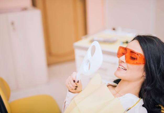 Weiblicher patient, der spiegel im zahnmedizinischen büro betrachtet