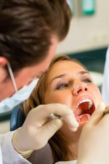 Weiblicher patient mit dentista zahnmedizinischer behandlung, tragenden masken und handschuhen