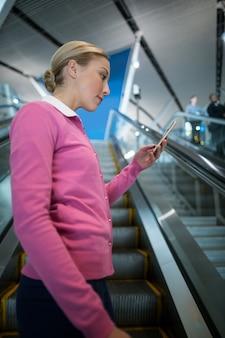 Weiblicher pendler, der handy auf rolltreppe benutzt