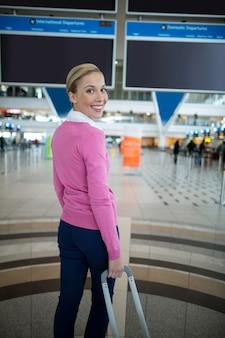 Weiblicher pendler, der mit gepäck am wartebereich im flughafen steht