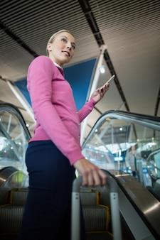 Weiblicher pendler mit gepäck unter verwendung des mobiltelefons auf rolltreppe