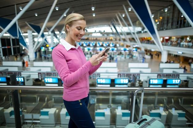Weiblicher pendler mit gepäck unter verwendung des mobiltelefons