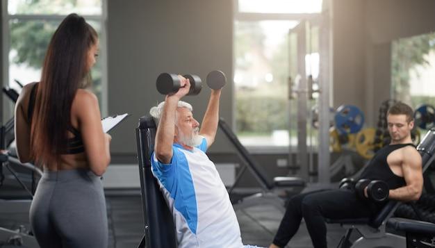Weiblicher persönlicher trainer, kunden beobachtend, übungen zu tun.