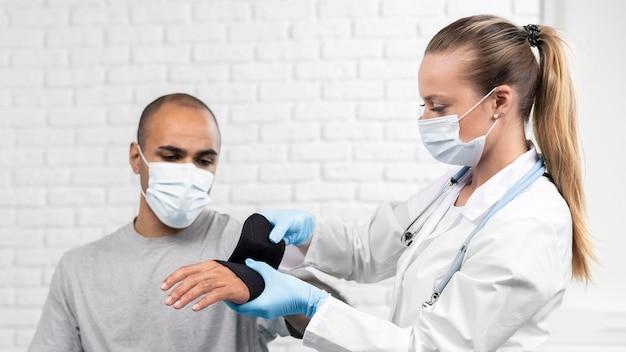 Weiblicher physiotherapeut, der das handgelenk des mannes einwickelt