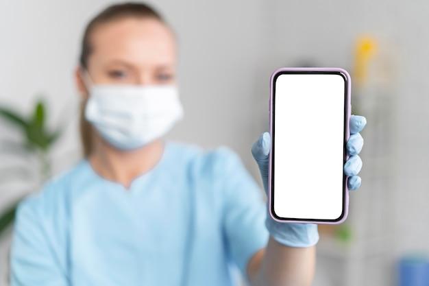 Weiblicher physiotherapeut mit medizinischer maske, die smartphone hält