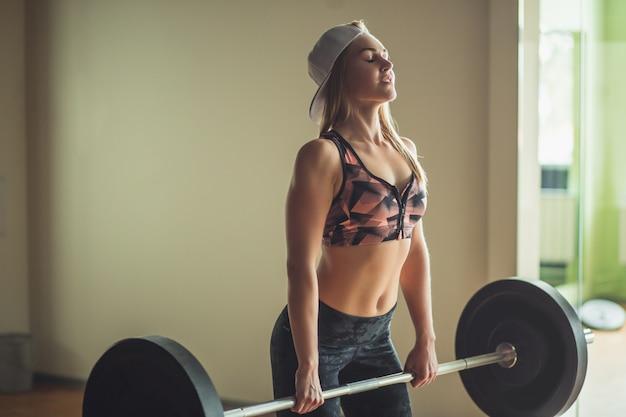 Weiblicher powerlifter, der sich auf kreuzheben der langhantel während des wettkampfs des powerlifting vorbereitet