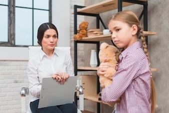 Weiblicher Psychologe, der eine Therapiesitzung mit dem traurigen Mädchen hält Teddybär in der Hand hat