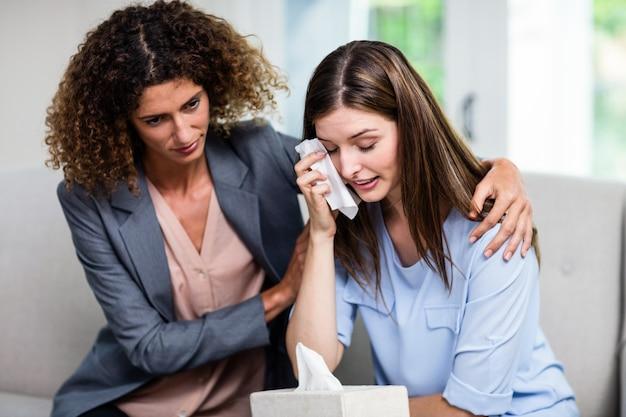 Weiblicher psychologe, der zu hause deprimierte frau auf sofa tröstet