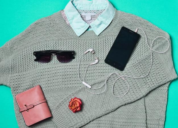 Weiblicher pullover, hemd, geldbörse, smartphone, kopfhörer, sonnenbrille auf blauem grund ausgelegt. kleidung und accessoires. draufsicht.
