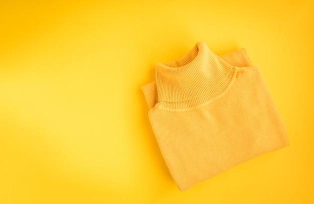 Weiblicher pullover und stiefel auf gelbem hintergrund. herbststil. warmes outfit für kaltes wetter. kleidung einkaufen, verkaufen, stil in trendigen farben konzept