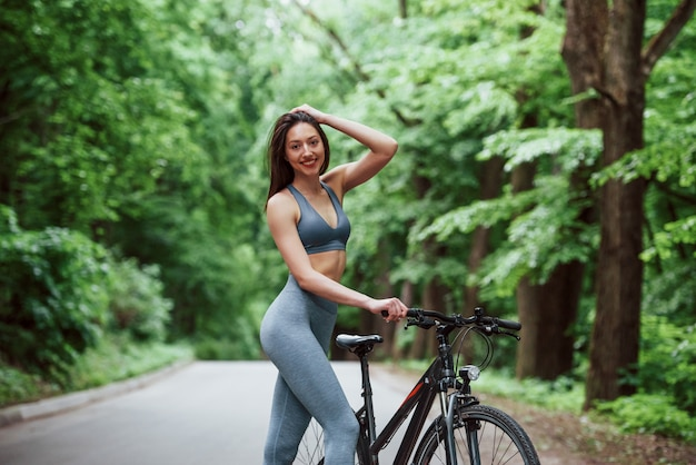 Weiblicher radfahrer, der mit fahrrad auf asphaltstraße im wald am tag steht