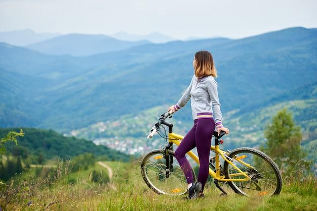 Weiblicher radfahrer, der mit gelbem fahrrad auf einem gras in der spitze des berges am bewölkten abend steht. berge, wälder und kleine stadt auf dem unscharfen hintergrund