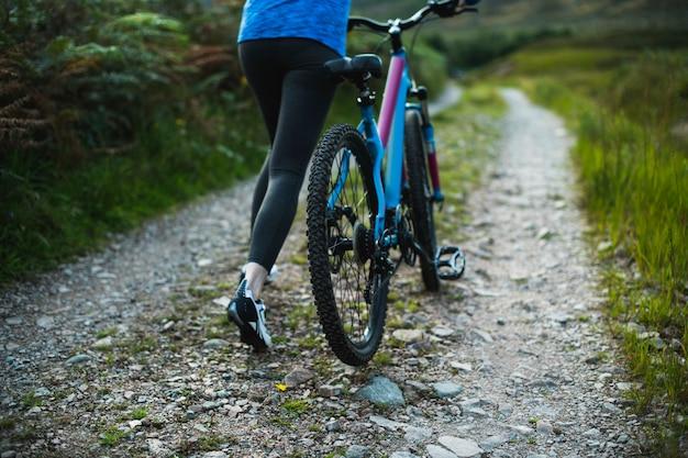 Weiblicher radfahrer, der mit ihrem fahrrad geht