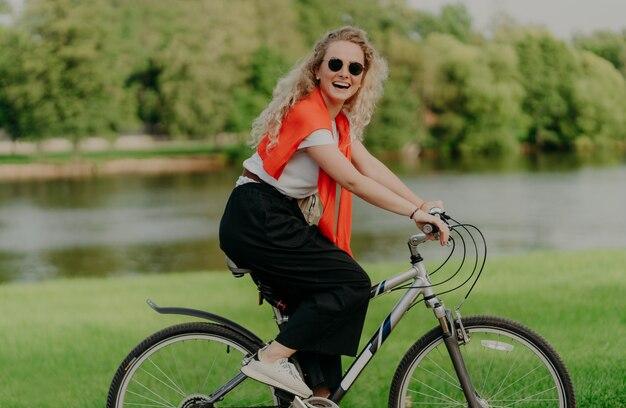 Weiblicher radfahrer fährt fahrrad, betrachtet kamera mit lächeln, trägt zufällige tägliche kleidung