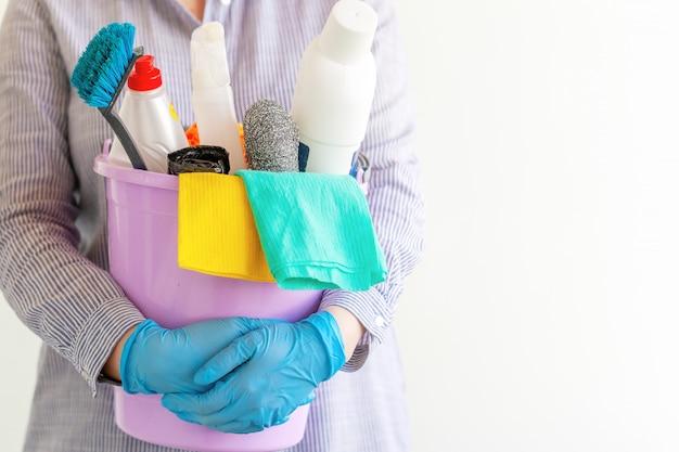 Weiblicher reiniger, der einen eimer mit putzzeug hält.