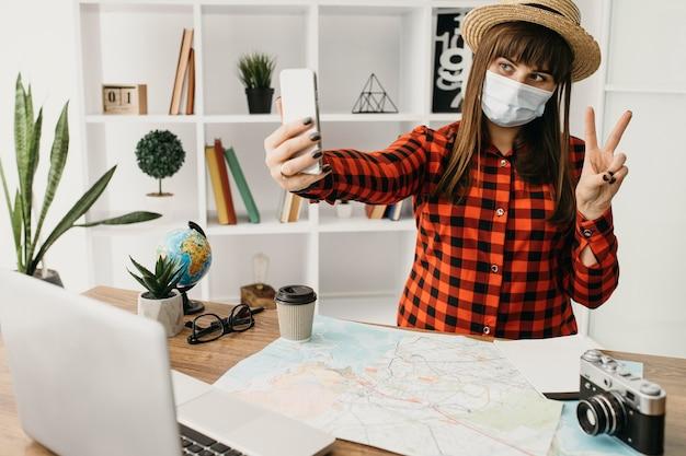 Weiblicher reiseblogger mit medizinischer maske, die mit laptop strömt