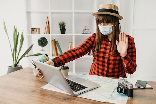 Weiblicher reiseblogger mit medizinischer maske, die mit laptop zu hause strömt