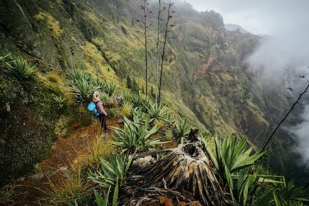 Weiblicher reisender, der am rand des buchtvulkans über dem nebligen grünen tal bleibt, das mit den agaven der insel santo antao in cabo verde bewachsen ist.
