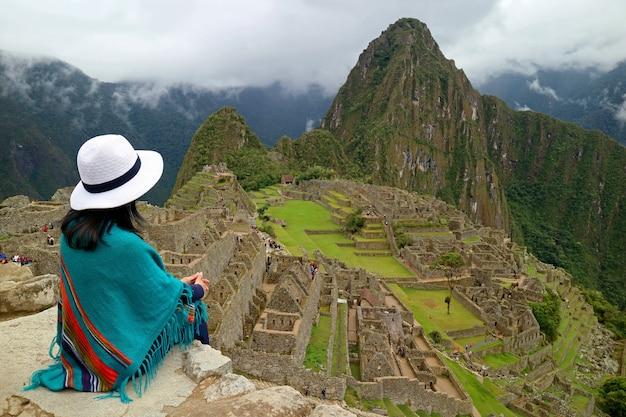 Weiblicher reisender, der auf cliff looking an den inkaruinen von machu picchu, peru sitzt