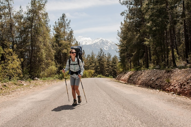Weiblicher reisender, der auf einen waldweg geht