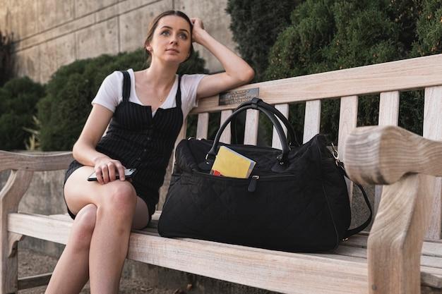 Weiblicher reisender, der auf einer bank sitzt