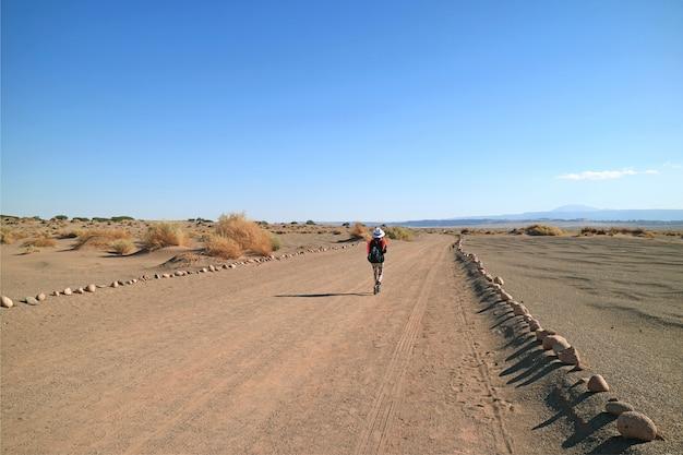 Weiblicher reisender, der auf wüstenstraße der archäologischen stätte aldea de tulor geht