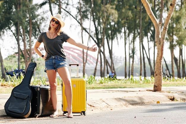 Weiblicher reisender, der auto fängt