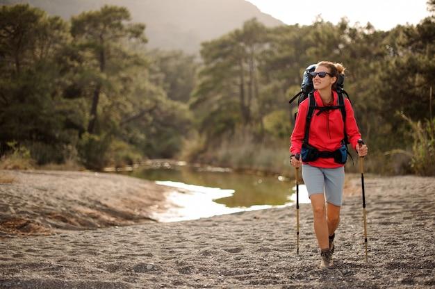 Weiblicher reisender, der durch waldflussufer geht
