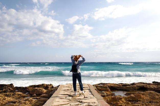 Weiblicher reisender, der einen meerblick bewundert. tourismus in zypern. mädchen reist an den stränden. junge schöne hipster-frau am tropischen strand, sommerferien, glücklich, spaß, genießen, sonnenstrahl, sonnig.
