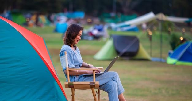 Weiblicher reisender, der neben campingzelt sitzt und notebook-laptop-computer arbeitet, der mit anderen zelten arbeitet, verwischt im hintergrund.